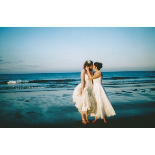 Two brides kiss on the beach