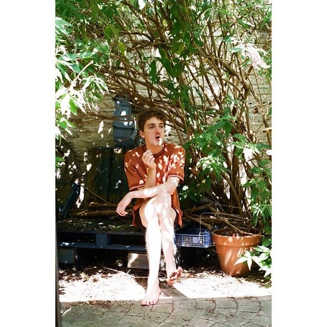 Man smoking under a bush