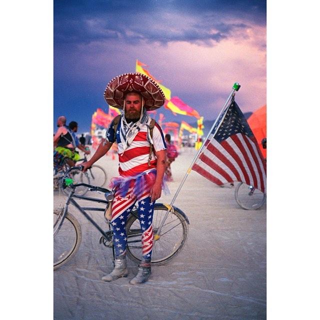 American man stood with bike